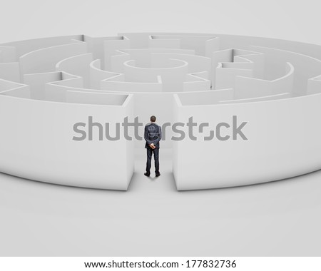 Successful businessman standing near the entrance of labyrinth