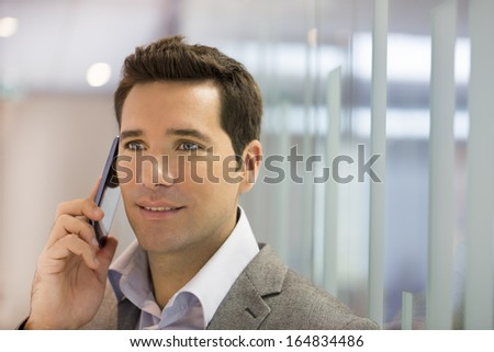 Successful businessman talking on cell phone in office  - stock photo