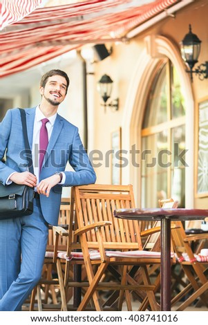 Successful businessman walking by street near french cafe at the early morning. Urban, city life. Happy handsome man. - stock photo