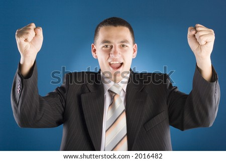 successful businessman with both hands up (blue background) - stock photo
