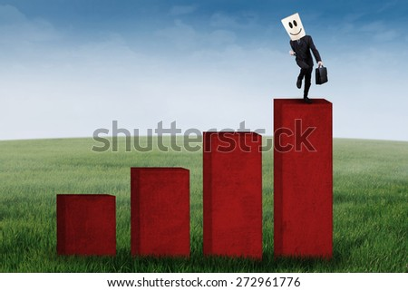 Successful businessman with cardboard head on the top of highest graph - stock photo