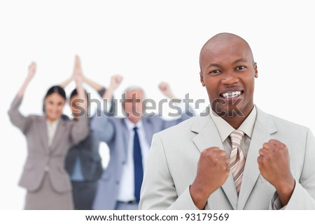 Successful businessman with cheering team behind him against a white background - stock photo