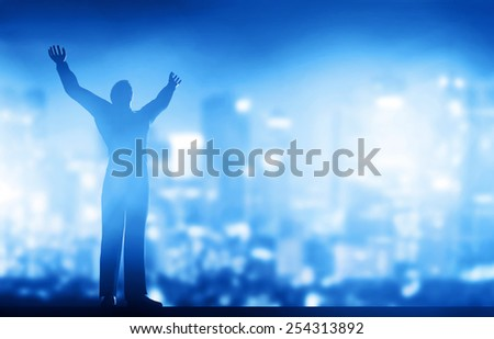 Successful businessman with hands up against city downtown at night background. Conceptual - stock photo