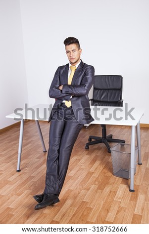 Successful businessman with his arms crossed at his office - stock photo