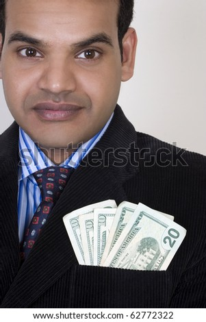 successful businessman with money in pocket - stock photo