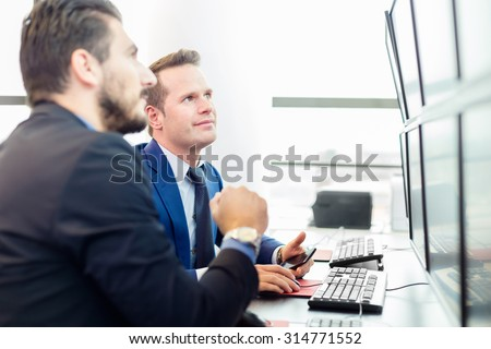 Successful businessmen trading stocks. Stock traders looking at graphs, indexes and numbers on multiple computer screens. Colleagues in traders office. Business success.  - stock photo