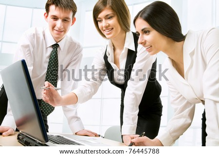 Successful businesspeople looking at monitor of computer - stock photo
