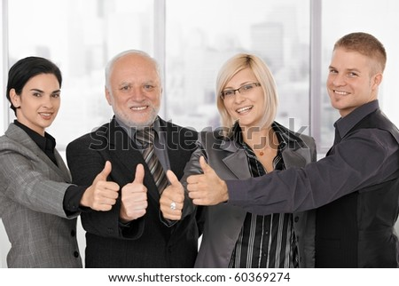 Successful businessteam of different generations smiling, giving thumb ups.? - stock photo