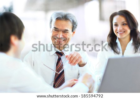 Successful businessteam of three sitting in office and planning work - stock photo