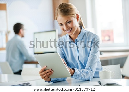 Successful businesswoman at work. Joyful young businesswoman in formalwear working on digital tablet and smiling while working in the office - stock photo