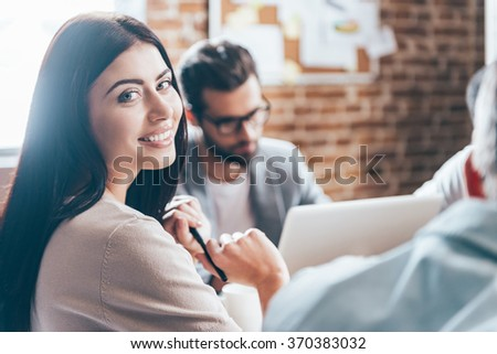 Successful businesswoman. Close-up of cheerful young woman looking at camera with smile while her colleagues discussing something in the background  - stock photo