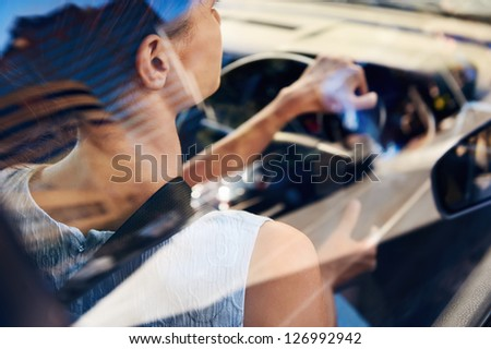 successful businesswoman driving car through modern urban city with reflections of buildings - stock photo