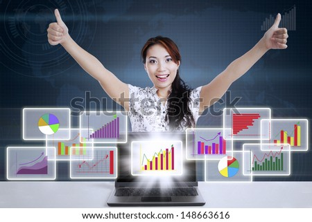 Successful businesswoman giving thumbs-up with different types of diagrams in 3d space - stock photo
