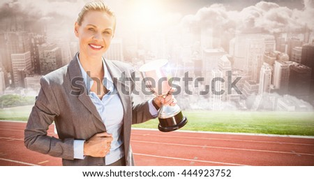 Successful businesswoman holding a trophy against composite image of track against city - stock photo