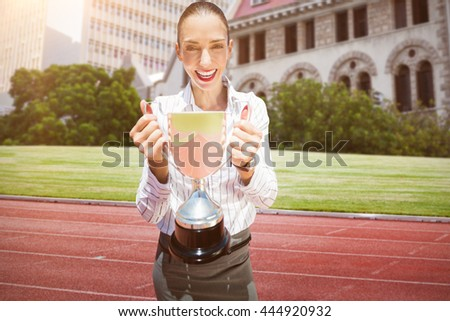 Successful businesswoman holding a trophy against running track in front of city - stock photo