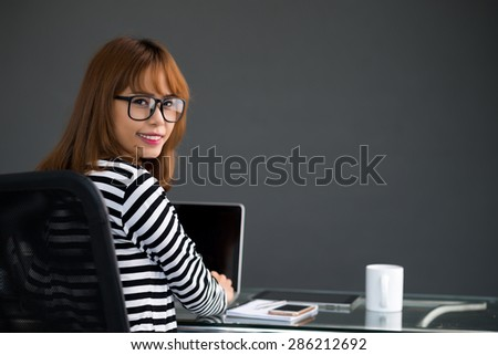 Successful businesswoman in glasses smiling and looking at camera