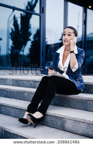 Successful businesswoman or entrepreneur taking notes and talking on cellphone while walking outdoor. City business woman working.