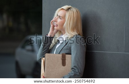 Successful businesswoman or entrepreneur talking on cellphone while standing outdoor. City business woman working. - stock photo