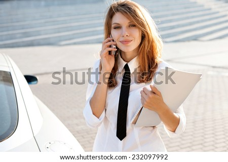 Successful businesswoman or entrepreneur talking on cellphone while walking outdoor. City business woman working / talkative woman in a white button down shirt with black tie   - stock photo