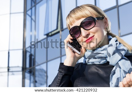 Successful businesswoman or entrepreneur tolling on phone while walking outdoor. City business woman working. - stock photo