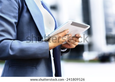Successful businesswoman or entrepreneur using a digital tablet computer, standing in front of her office. - stock photo