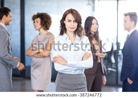 Successful businesswoman smiling at camera while her colleagues interacting with each other in background