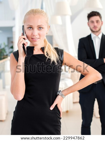 Successful businesswoman. Successful businessman standing in an office and looking at the camera with a mobile phone in her hand while her colleagues standing behind her - stock photo