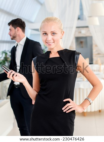 Successful businesswoman. Successful businessman standing in an office and looking at the camera with a mobile phone in her hand while her colleague talking on the background - stock photo