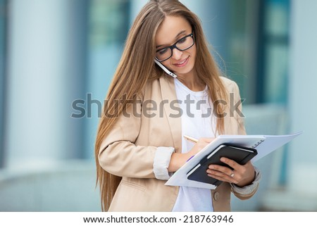 Successful businesswoman talking on cellphone while walking outdoor. City business woman working. - stock photo