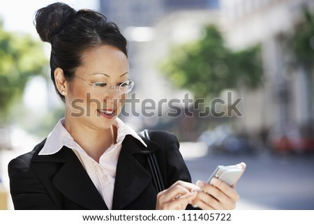 Successful businesswoman using cell phone - stock photo