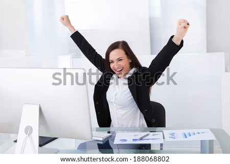 Successful businesswoman with arms raised sitting at desk in office