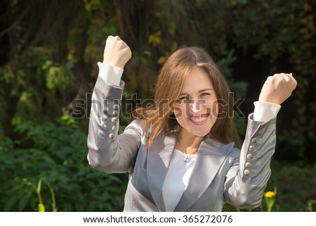 Successful businesswoman with hands raised celebrating achievement outdoors.