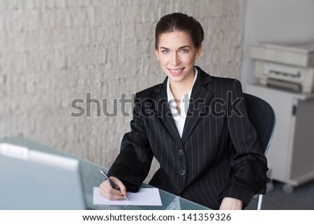 Successful businesswoman with teeth smile in office, signing document