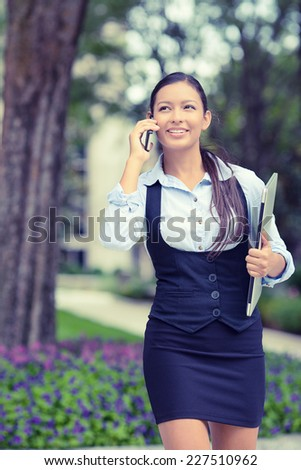 Successful businesswoman young entrepreneur talking on cellphone while walking outdoor  holding computer laptop in hand. City business woman working outside on street in park. Positive face expression - stock photo