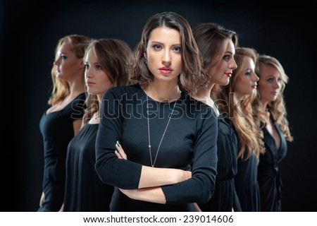 Successful caucasian business woman leading a team. Confident young woman in black dress looking at camera with arms folded and her friends standing in front her back against black background. - stock photo