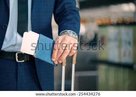 Successful check-in. Cropped image of a handsome young businessman in suit looking at his watch and holding his passport with a ticket while standing in the airport with his luggage - stock photo