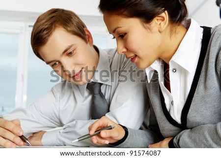 Successful colleagues working with papers in office - stock photo