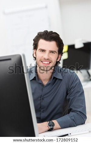 Successful confident businessman with a warm friendly smile sitting at his desk in the office looking at the camera - stock photo