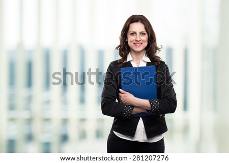 Successful confident middle age businesswoman smiling in her office, holding a file in her hands. - stock photo