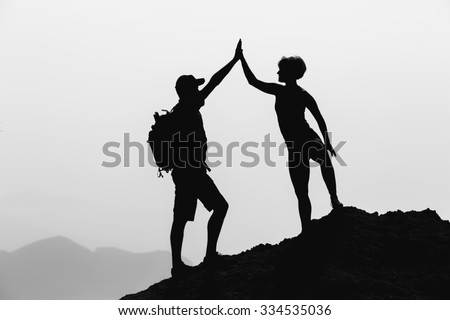 Successful couple achievement climbing or hiking, business concept with man and woman celebrating with arms up raised outstretched outdoors - stock photo