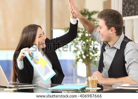 Successful coworker showing a growth graph celebrating good results and giving high five in an office interior - stock photo