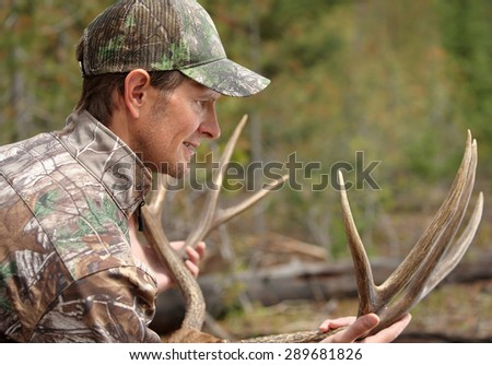 successful deer hunter inspecting antlers - stock photo