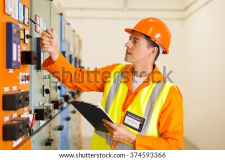 successful electrical engineer writing down machine setting data
