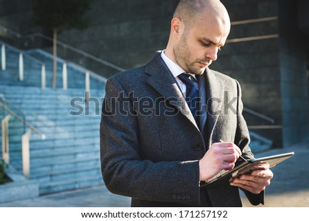 successful elegant fashionable businessman using tablet  in business district - stock photo