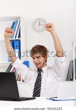 Successful excited young business man happy smile sitting at the desk hold raised arms hand up using computer, handsome businessman working on laptop, using computer, concept of success, victory, win - stock photo
