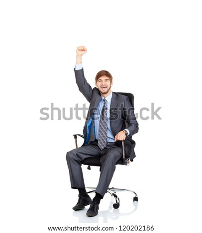 successful excited young businessman sitting in chair smile with raised arm fist, portrait of business man hold hand up in air, full length isolated over white background - stock photo
