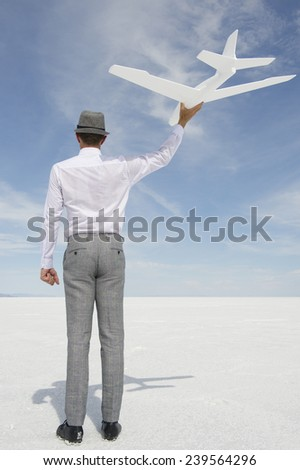 Successful executive businessman flying white model airplane against blue sky - stock photo