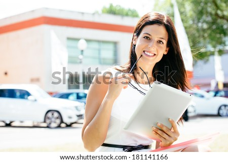 Successful female car sales consultant in business trade fair showing blank digital tablet screen and approving with thumbs up. Vehicle offer and information concept. - stock photo