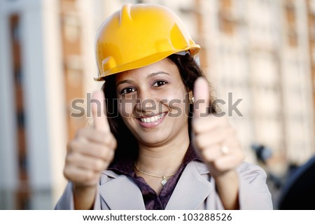 Successful female construction engineer showing thumbs up - stock photo