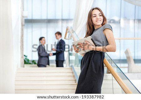 Successful girl! Woman businessman stands on the stairs looking at the camera.Beautiful business woman girl holding a tablet in her hands and smiling in camera.In the background are two businessman